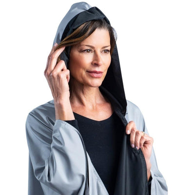 Women wearing a hooded Black & Pewter Grey RainCaper travel cape with the Pewter Grey color side out