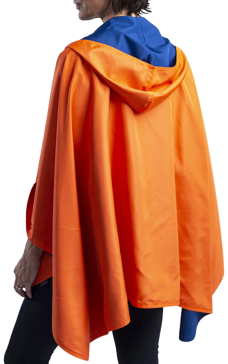 Woman wearing a Navy Blue & Orange Wind & Rainproof Sports Cape with  the Navy Blue side out, revealing the Orange  print at the lapels,neckline and cuffs