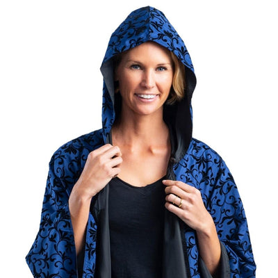 Women wearing a hooded Midnight Blue with Velvet Swirls RainCaper travel cape with the Velvet Swirls print side out