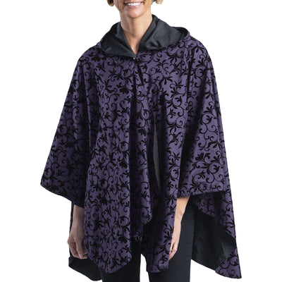 Women wearing a Plum with Velvet Swirls RainCaper travel cape with the Velvet Swirls side out, revealing the Plum side at the lapels, neckline and cuffs
