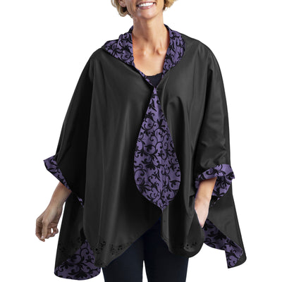 Women wearing a Plum with Velvet Swirls RainCaper travel cape with the Plum side out, revealing the Velvet Swirls print at the lapels and neck