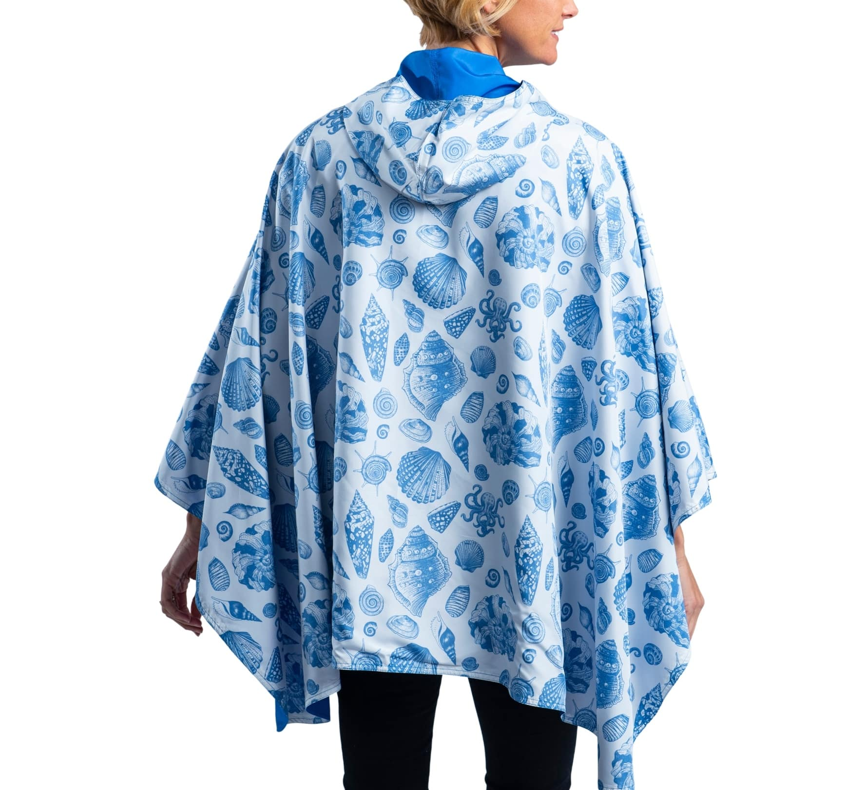 Women wearing an Ocean with Seashells & Tiny Octopus RainCaper travel cape with the Ocean side out, revealing the Seashells & Tiny Octopus print at the lapels and cuffs