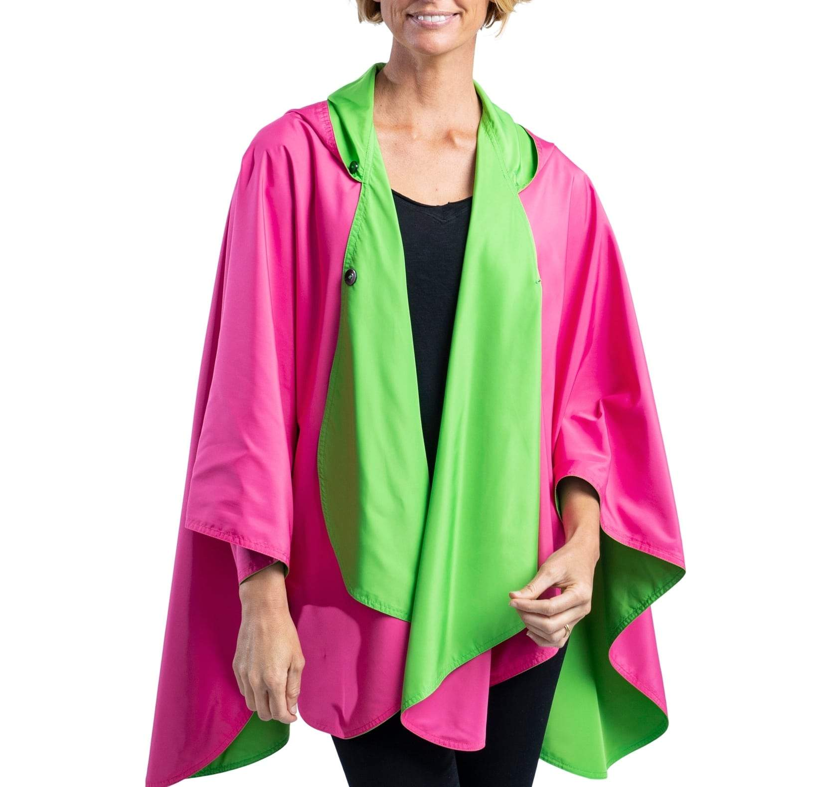 Women wearing a Hot Pink & Lime Green RainCaper travel cape with the Hot Pink side out, revealing the Lime Green color at the lapels and neck