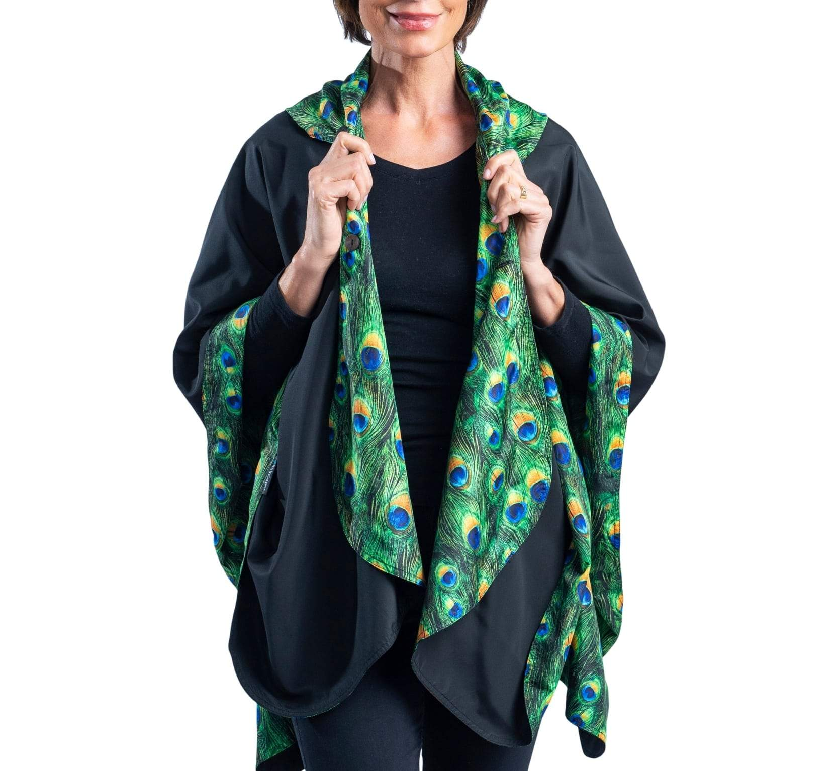 Women wearing a Black & Peacock RainCaper travel cape with the Black side out, revealing the Peacock print at the lapels and cuffs