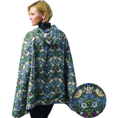 Woman wearing a Black/William Morris Strawberry Thief cape which reverses to Black. She is standing with a blow-up of the William Morris Strawberry Thief print detail.