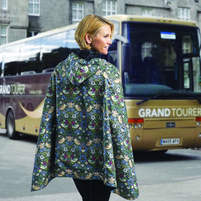 Women wearing a Black/William Morris Strawberry Thief RainCaper travel cape. Women is walking towards the bus.