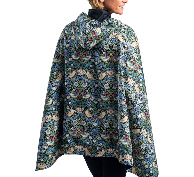 Women wearing a Black/William Morris Strawberry Thief RainCaper travel cape with the Black side out, revealing the William Morris Strawberry Thief print at the lapels and cuffs