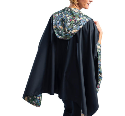 Women wearing a hooded Black/William Morris Strawberry Thief RainCaper travel cape with the William Morris Strawberry Thief print side out