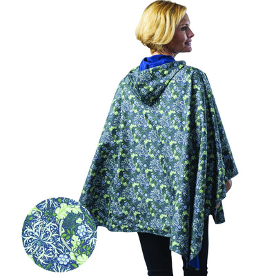 Woman wearing a Navy/William Morris Seaweed cape which reverses to Navy. She is standing with a blow-up of the William Morris Seaweed print detail.