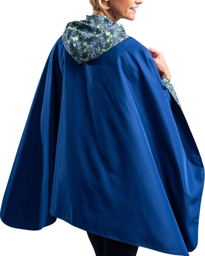 Women wearing a Navy/William Morris Seaweed RainCaper hooded travel cape with the Navy side out