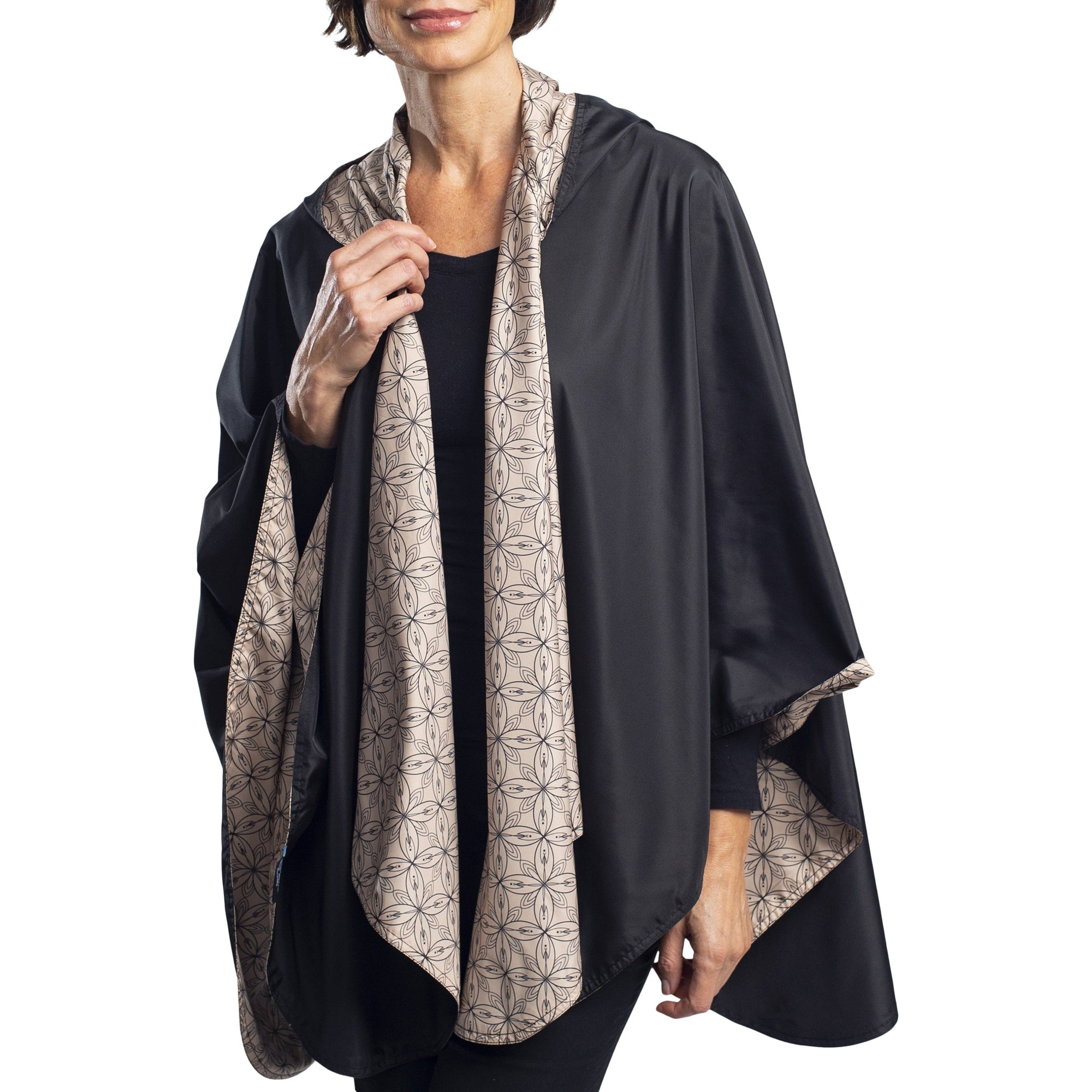 Women wearing a Black/Camel Kelsey Print RainCaper travel cape with the Black side out, revealing the Camel Kelsey print at the lapels and cuffs
