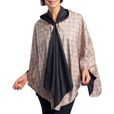 Women wearing a Black/Camel Kelsey Print RainCaper travel cape with the Camel Kelsey side out, revealing the Black side at the lapels, neckline and cuffs