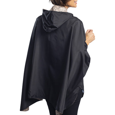 Women wearing a Black/Camel Kelsey Print RainCaper hooded travel cape with the black side out