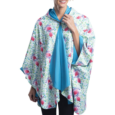 Women wearing an Aqua & Spring Watercolor RainCaper travel cape with the Spring Watercolor side out, revealing the Aqua side at the lapels, neckline and cuffs