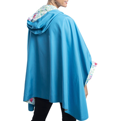 Women wearing an Aqua & Spring Watercolor RainCaper travel cape with the Aqua side out, revealing the Spring Watercolor print on the hood and cuffs