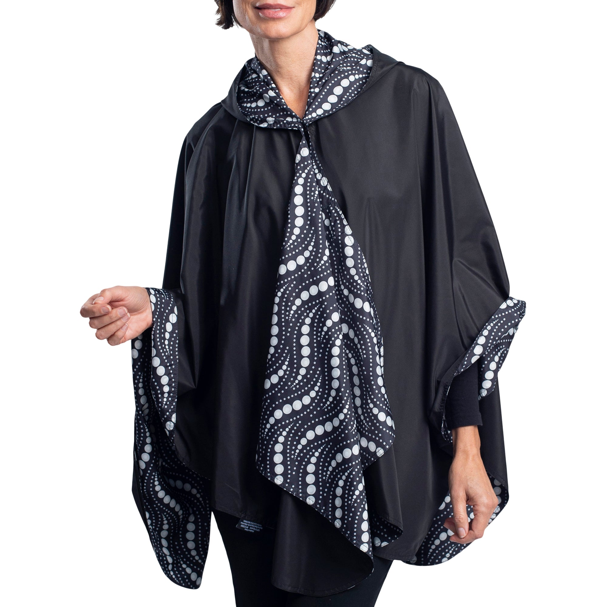 Women wearing a Black/Wavy Pearls Reversible RainCaper travel cape with the Black side out, revealing the Wavy Pearls print at the lapels and cuffs
