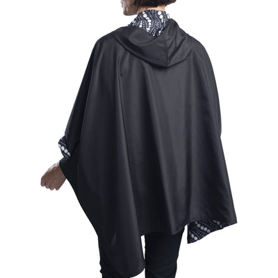 Women wearing a Black/Wavy Pearls Reversible RainCaper hooded travel cape with the black side out