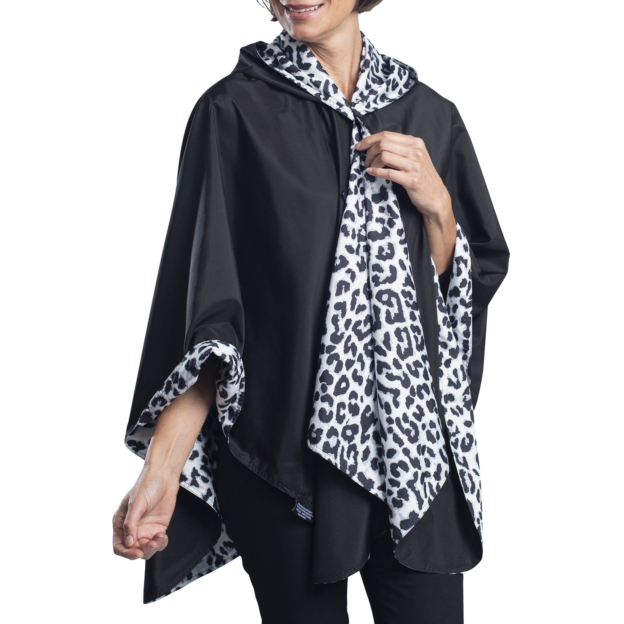 Women wearing a Black and White Animal Print RainCaper travel cape with the Black side out, revealing the White Animal print at the lapels and cuffs