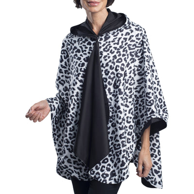 Women wearing a Black and White Animal Print RainCaper travel cape with the White animal Print side out, revealing the Black side at the lapels, neckline and cuffs