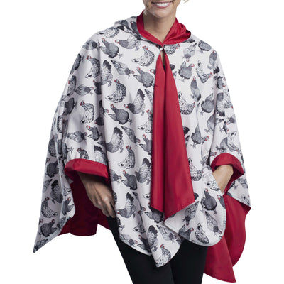 Women wearing a Crimson/Hens & Chickens Reversible RainCaper travel cape with the Hens & Chickens side out, revealing the Crimson side at the lapels, neckline and cuffs
