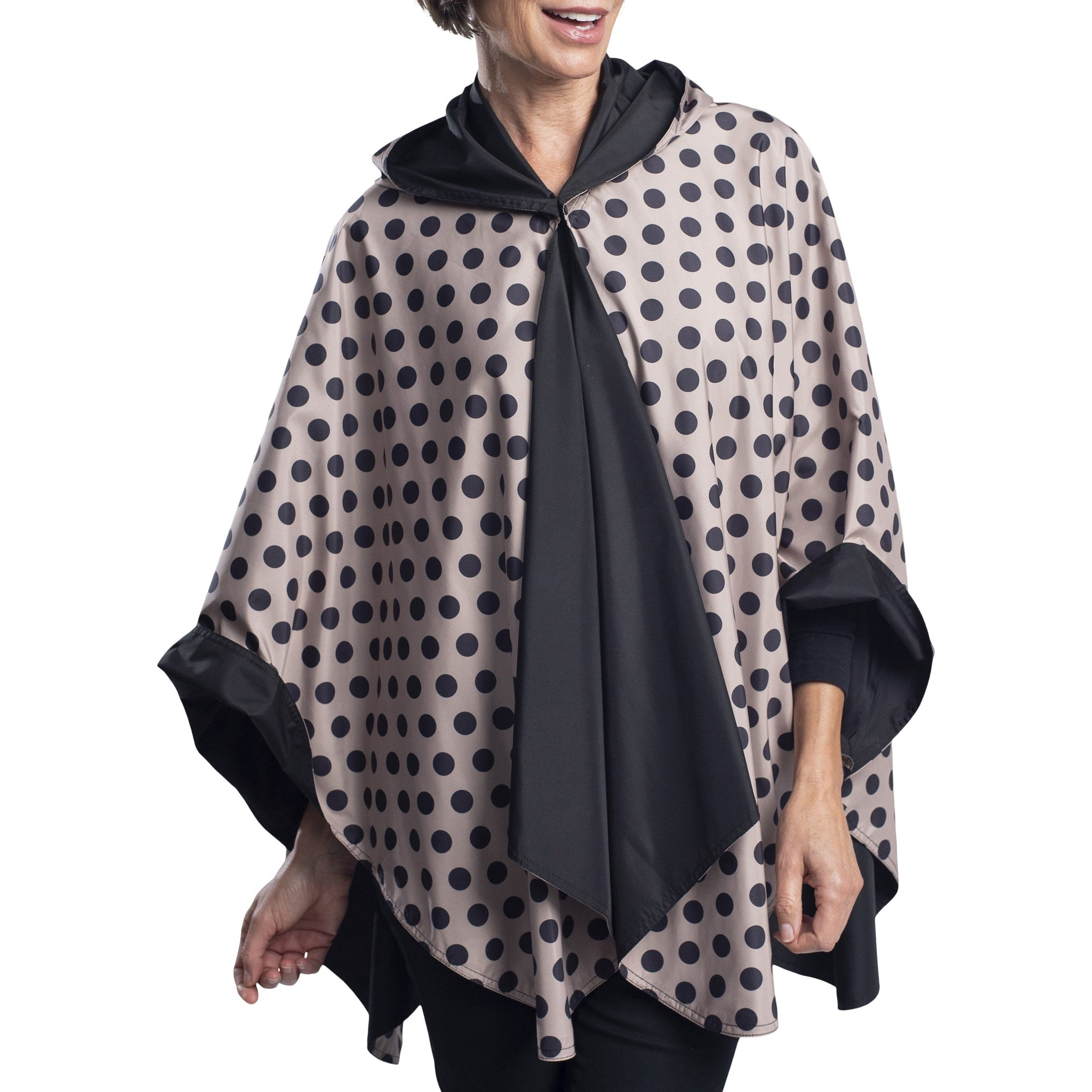 Women wearing a Black and Camel Dots Reversible RainCaper travel cape with the Black side out, revealing the Camel Dots Reversible print at the lapels and cuffs