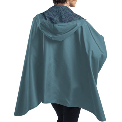 Women wearing a Soft Teal & Circle Dots Reversible RainCaper travel cape  revealing the Soft Teal side.
