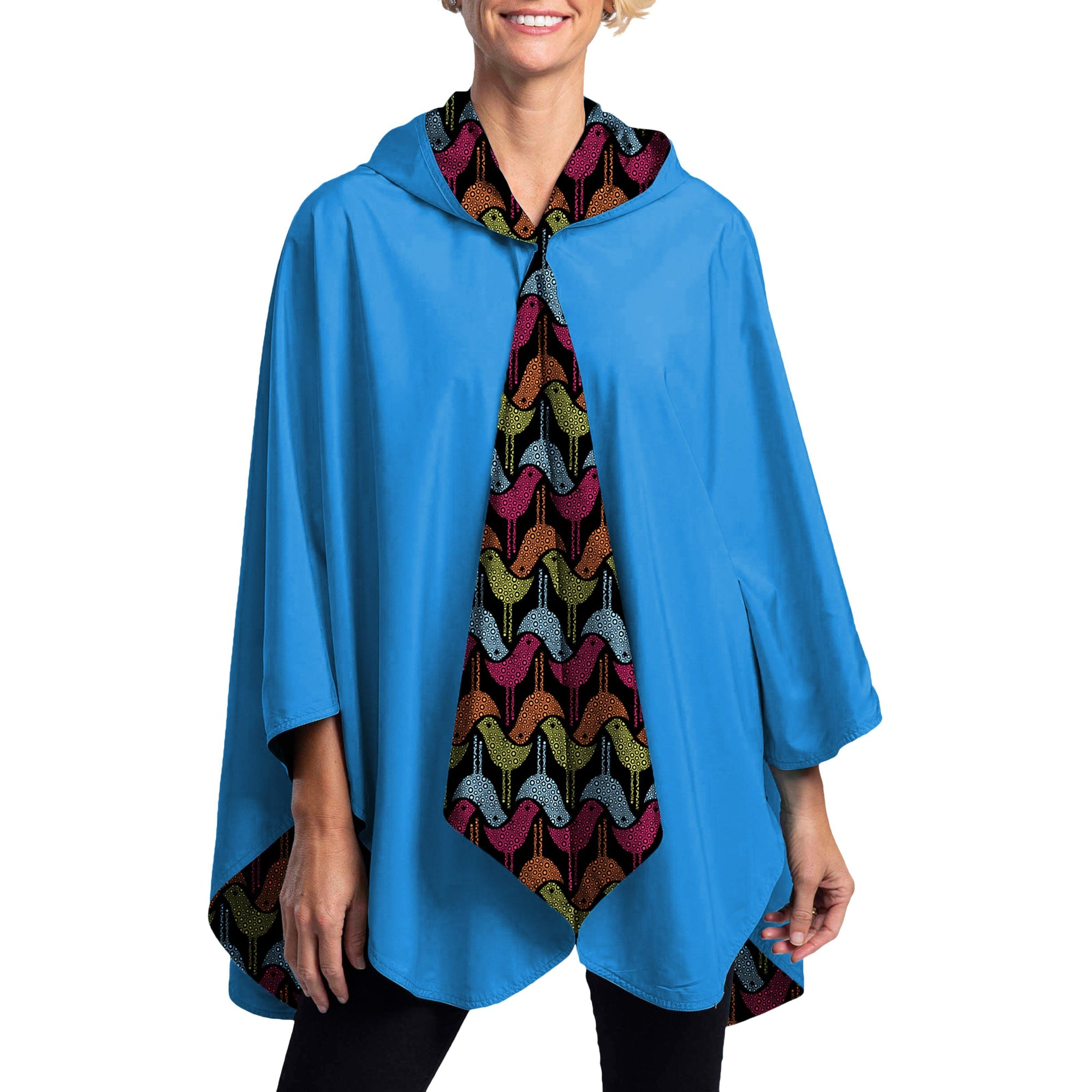 Women wearing a Bluebird & Birds RainCaper travel cape with the Birds side out, revealing the Bluebird color at the lapels and cuffs