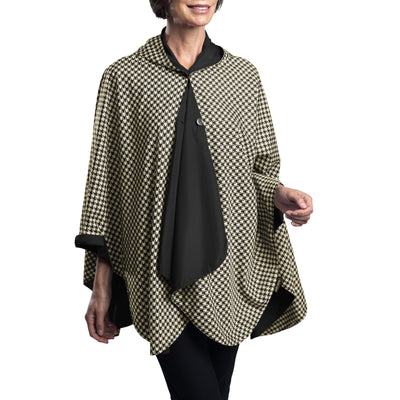 Women wearing a Black & Camel Houndstooth RainCaper travel cape with the Camel Houndstooth side out, revealing the Black side at the lapels, neckline and cuffs.