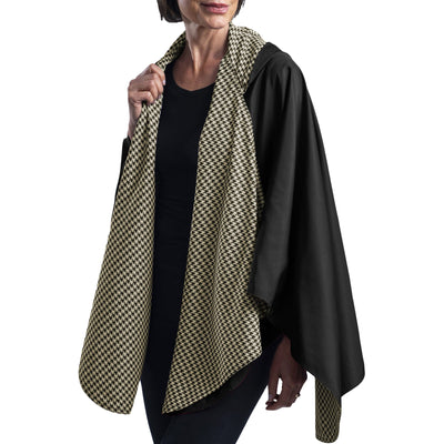 Women wearing a Black and Camel Houndstooth RainCaper travel cape with the Black side out, revealing the Camel Houndstooth print at the lapels and cuffs.