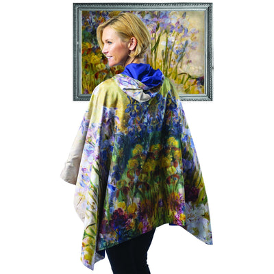 Woman wearing a RainCaper Tiffany Peonies & Iris travel cape which reverses to Iris. She is standing in front of a framed image of Tiffany Peonies & Iris oil painting which inspired the Tiffany Peonies & Iris RainCaper.