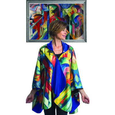 Woman wearing a WarmCaper Franz Marc Stables travel cape which reverses to Royal. She is standing in front of a framed image of Franz Marc Stables oil painting which inspired the Franz Marc Stables WarmCaper.