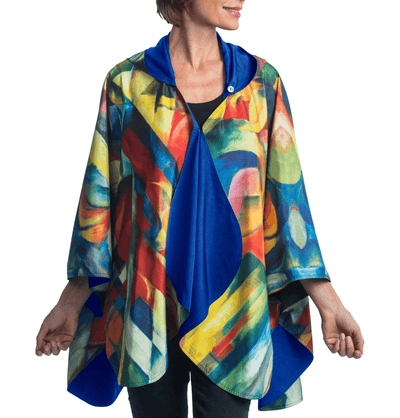 Woman wearing a RainCaper Franz Marc's Stables travel cape.