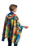 "Woman wearing a WarmCaper Royal/Franz Marc ""Stables"" lined rain and travel cape by RainCaper.  The rainproof side features a Royal/Franz Marc ""Stables"" print while the warm side is royal."