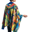 Woman wearing a RainCaper Franz Marc's Stables travel cape which reverses to Royal.