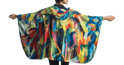 Woman wearing a RainCaper Franz Marc Stables travel cape.