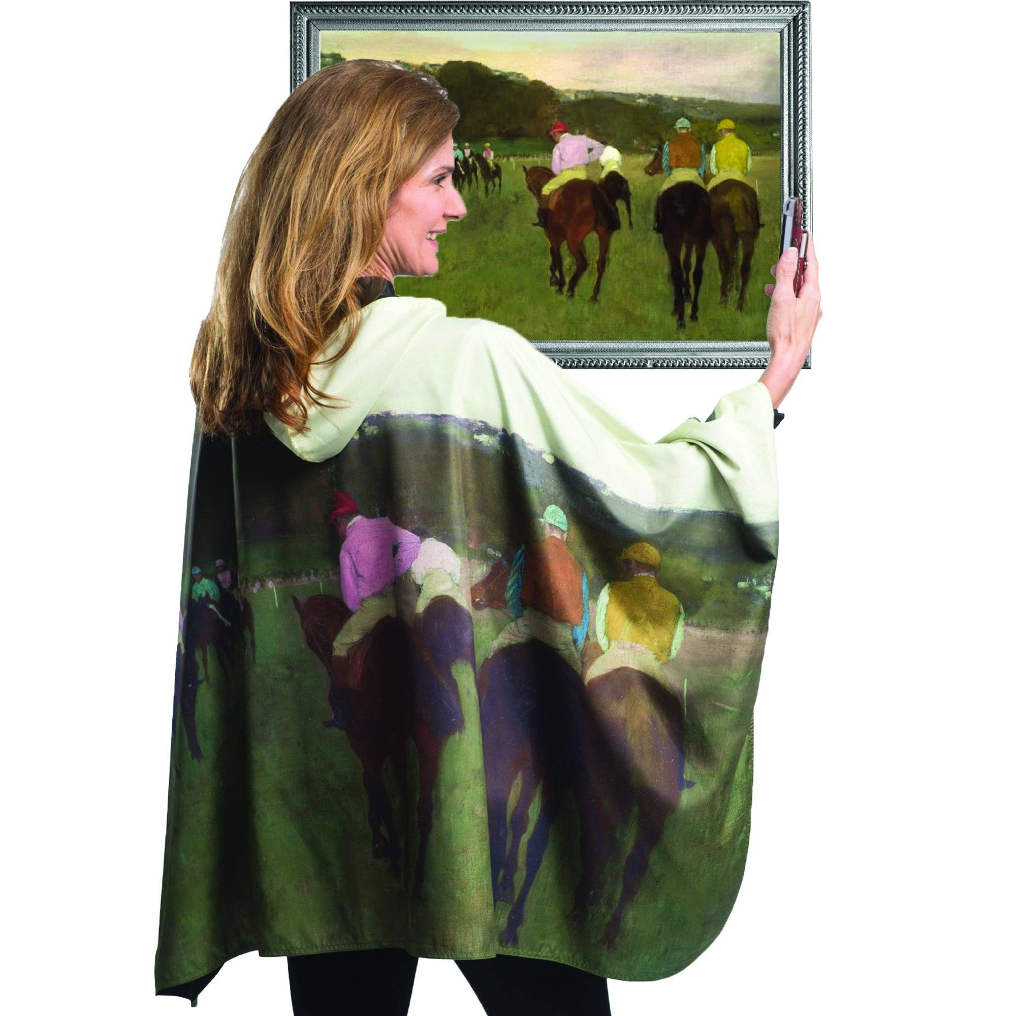 Woman wearing a WarmCaper Degas Racehorses at Longchamp travel cape which reverses to Black. She is standing in front of a framed image of Degas Racehorses at Longchamp oil painting which inspired the Degas Racehorses at Longchamp WarmCaper.