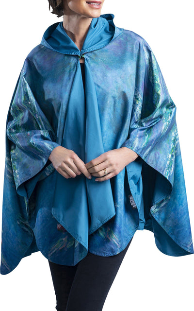 Woman wearing a RainCaper Monet Water Lilies travel cape which reverses to Soft Teal.