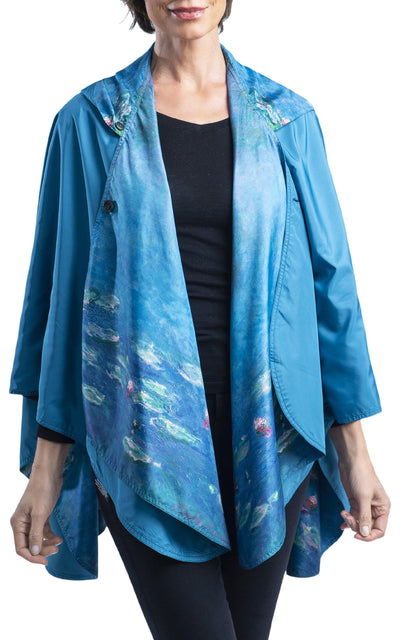 Woman wearing a RainCaper Monet Water Lilies travel cape. The cape reverses to Soft Teal when reversed,  the Monet Water Lilies print is visible on the lapels and hood.
