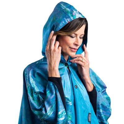 Woman wearing a RainCaper Monet Water Lilies hooded travel cape which reverses to Soft Teal.