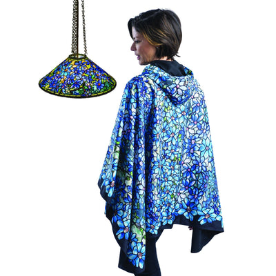 Woman wearing a WarmCaper Tiffany Clematis travel cape which reverses to Black. She is standing in front of a Tiffany Clematis oil painting which inspired the Tiffany Clematis WarmCaper.