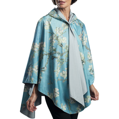 Woman wearing a RainCaper van Gogh Almond Blossom Travel Cape which reverses to Bark.