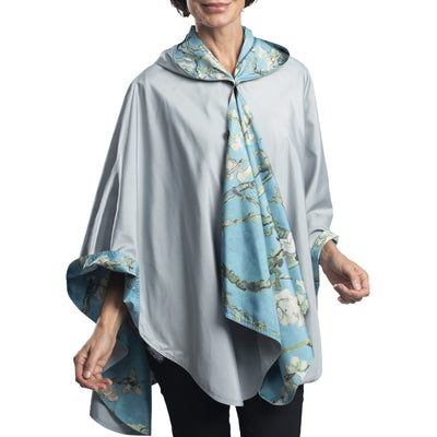 Woman wearing a RainCaper van Gogh Almond Blossom Travel Cape. The cape reverses to Bark; when reversed, the van Gogh Almond Blossom Travel Cape print is visible on the lapels and hood.