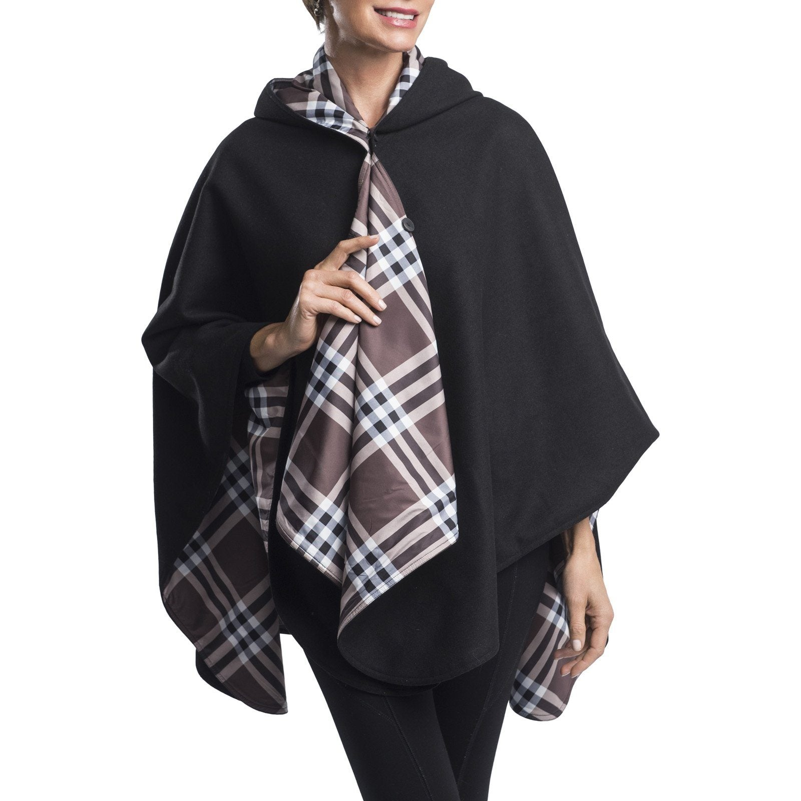 Woman wearing a WarmCaper Rainproof Black & Coco Plaid rain and travel cape. The reversible cape is warm black; the Rainproof Coco Plaid print is visible on the hood and lapels