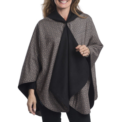 Woman wearing a WarmCaper Black / Camel Diamonds lined rain and travel cape by RainCaper.  The rainproof side features a Black / Camel Diamonds print while the warm side is black.