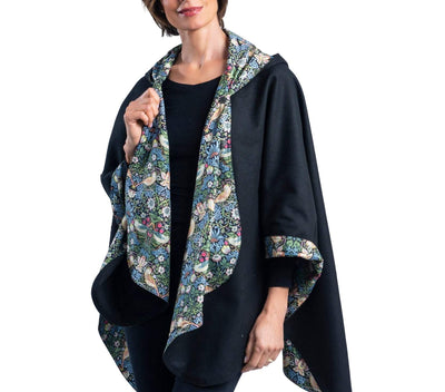 Woman wearing a WarmCaper Rainproof William Morris Strawberry Thief print rain and travel cape. The reversible cape is warm black; the Rainproof Strawberry Thief print is visible on the hood, lapels and cuffed arms.