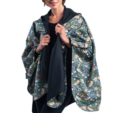 Woman wearing a WarmCaper Warm Black & Rainproof William Morris Strawberry Thief print  lined rain and travel cape by RainCaper.