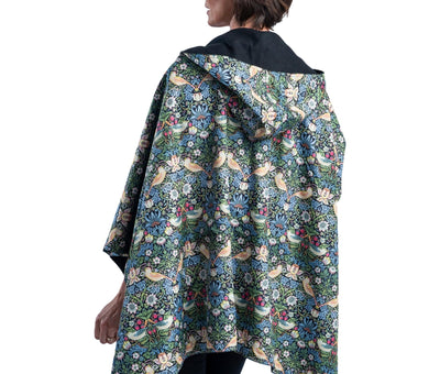 Woman wearing a WarmCaper Rainproof William Morris Strawberry Thief print lined rain and travel cape by RainCaper.