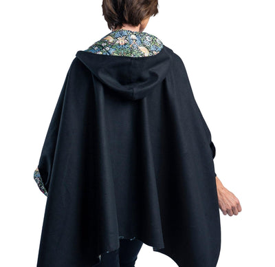 Woman wearing a WarmCaper Rainproof William Morris Strawberry Thief print rain and travel cape. The reversible cape is warm black; the Rainproof William Morris Strawberry Thief print is visible on the hood and cuffed arms.