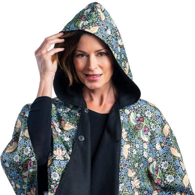 Woman wearing a WarmCaper Rainproof William Morris Strawberry Thief hooded rain and travel cape which reverses to a warm black.