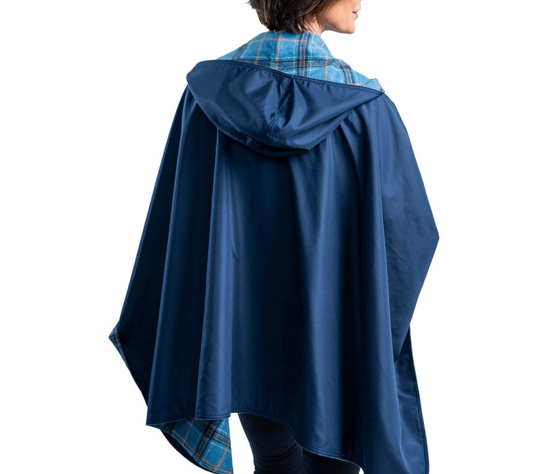Woman wearing a WarmCaper Warm Blue Plaid/Rainproof Navy rain and travel cape. The reversible cape is warm Blue Plaid;the Rainproof Navy print is visible on the hood and lapels.